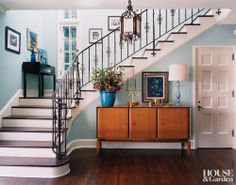 The ornate iron banister and lantern in a Minneapolis entry pop against sky blue walls.