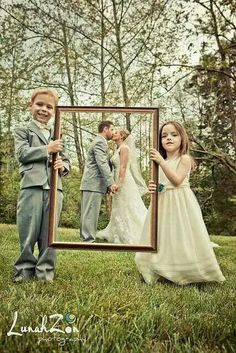 Flower girl and page boy holding up picture frame with bride and groom behind it