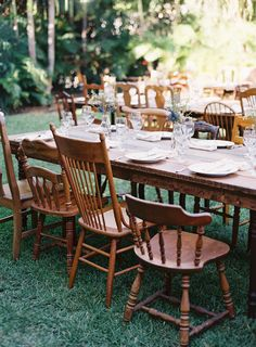 Mismatched wooden chairs surrounding a wooden table make the perfect outdoor wedding reception dining arrangements.  Love the bare wood tables and simple flower vase centerpieces!  #rusticwedding #receptiondecor #mwri