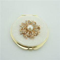 Jewelled Enamel Compact Mirror/Cosmetic Mirror This high fashion compact mirror is a perfect gift for lady. It is covered with ivory enamel glaze and mounted with bling-bling crystals.