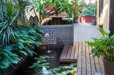 Deze tuin wordt gekenmerkt door de tropische sfeer. Dit komt naar voren in de houten meubels, warme kleuren op de muur, mozaïektegels bij het fonteintje. Donkerrood is in zowel op de muren als in de beplanting terug te vinden.