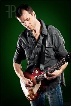 Picture of man with a guitar on a green background