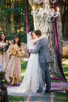 The wedding couple kissed beneath a crystal chandelier suspended from a tree. #BohoWedding #WeddingCeremony Photography: Amanda McKinnon Photography. Read More:  http://www.insideweddings.com/weddings/bride-wears-claire-pettibone-gown-to-bohemian-outdoor-wedding/668/