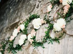 Floral hoop wedding ceremony altar arrangement made from cross stitch hoops, Italian ruscus greenery, white roses, white football mums, blush stock, spray roses, rose gold spray paint and copper wire. Flowers by Gold Leaf Floral // @goldleaffloral. Photo by Photos by Heart