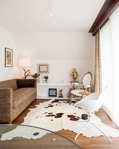 Decoração de chalé.  Na sala, sofá cinza, tapete de pele, luminária de mesa, cadeira de madeira, cadeira branca.    #decoracao #decor #details #casadevalentina