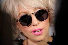 Lady Gaga Pink Lipstick - Lady Gaga always adds a shock of color to her look. The pop star paired her round glasses and blond tresses with hot pink lipstick in a matte texture. Anna Wintour, Lady Gaga Makeup, Superstar, Photo Star, Hot Pink Lipsticks, Full Hair, Portrait, Rose, Business Women