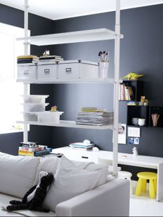 Using widely spaced open shelves to divide one room into two is easy with the IKEA STOLMEN shelving system.