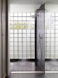 Une maison design parmi les arbres. POr si hace falta: baño con doble regadera. Pese a que tiene piso y muros oscuros, la pared lateral de vidrio emerilado en parte, deja pasar la luz...