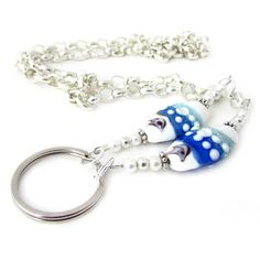 This pretty eyeglass lanyard features 2 gorgeous ocean colors lamp work beads. Stop losing those cheaters and wear a stylish beaded lanyard that is one of a kind. This also makes a pretty keychain or ID lanyard. This lanyard measures 16-1/2 inches when folded in half and is made using silver tone metal chain and 2 beautiful handmade lamp work beads - all the colors of the ocean and a tiny stingray shaped creature. There are matching sea colored chip beads to add to the beach theme. This ...