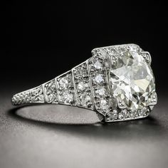 Hand-fabricated in platinum during the height of the Jazz Age - circa 1925 - this striking and impressive super-sparkler beams front and center with a gorgeous European-cut diamond weighing in at 2.14 carats. The scintillating stone is embellished all around with small bright white single-cut diamonds (totaling .60 carat) arrayed in a classic and striking geometric step design. A truly stunning original Art Deco dazzler. The currently ring size 6 1/4 ring shank is fully hand-engraved. Ac...