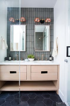 Modern bathroom with rose gold sconces, concrete tiles, and industrial silver mirrors
