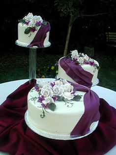 Instead of a tiered wedding cake, how about displaying the layers separately? This plum purple and white series of cakes features a consistent design of plum fondant ribbon and sugared roses.