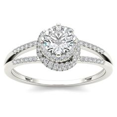 Timeless and elegant, this engagement ring is a look she'll adore. Made in white gold, the eye is drawn to the solitaire center stone wrapped by a frame of smaller diamonds that wrap the center stone,