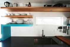 Create a contemporary look in your kitchen with textured glass tile and a few brightly colored floating shelves. If you're afraid to go completely wild, feel free to mix and match your bright shelves with traditionally finished ones.