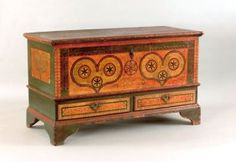 "Furniture: Lehigh County, Pennsylvania painted dower chest dated 1785, inscribed ""Sofia Refinger,"" the front decorated with two green sponge hearts, each with three pinwheels on a yellow and orange sponge ground with interlacing circle border, above two drawers supported by bracket feet."