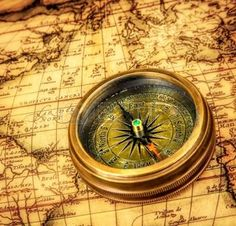 Vintage still life. Vintage compass lies on an ancient world map. photo