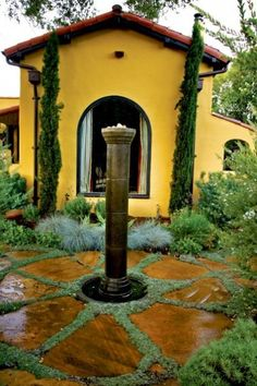 No lawn — instead, a tall water feature is set among adobe-color pavers edged with dymondia, a low-growing ground cover. Grasses and soft-color shrubs edge the space, allowing house color to be the single bold accen