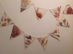 This pretty paper bunting has been up-cycled from an old copy of the book The Complete Book of Dried Flowers. Each flag features images of dried flowers in muted, warm colours. This bunting would look lovely at vintage or country themed weddings. This strand of bunting has 10 flags. The flags measure approximately 7 1/2 inches across and 8 inches long. The flags are strung onto white, natural cotton string. The string is approximately 3 meters long and the flags can be positioned anywhe...