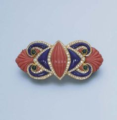 Christie's A CORAL, LAPIS LAZULI AND DIAMOND BROOCH Designed with carved coral palmettes, lapis lazuli scrolls within diamond borders to the cabochon emerald detail, mounted in 18k gold, 7.6 cm. long