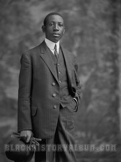 Portrait of an African American man wearing a pin-stripped, formal suit and holding a hat in his right hand, 1905.