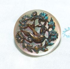 Antique Small MOP Button ~ Brass Escutcheon Flying Bird in a Floral Wreath by YesterYearsFindings on Etsy https://www.etsy.com/listing/256983135/antique-small-mop-button-brass