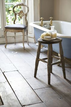 Nice mix of reclaimed floors, charming chair, simple stool and of course the blue clawfoot tub!