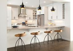 I love the pendants and stools in this kitchen. The white walls and cabinets act as a blank canvas, allowing the interesting fixtures and furnishings to really stand out.
