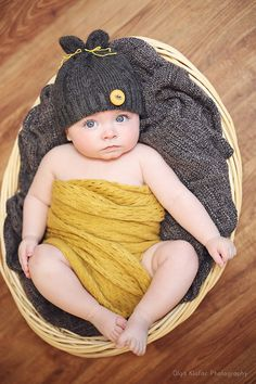 5-month-old baby boy lying in a basket wearing grey hat with yellow button, unique baby photos by Olga Klofac Professional Baby & Child Photographer Charlestown Mayo   www.mayophotographer.ie www.facebook.com/olgaklofacphotography