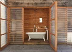 """The ultimate luxury: a hot bath in the clawfoot tub, with the fiberglass door open wide to the woods. Tagged: Bath Room and Freestanding Tub. Search """"Bathroom"""" from A Platform for Living. Browse inspirational photos of modern bathrooms. Indoor Outdoor, Outdoor Baths, Outdoor Bathrooms, Outdoor Showers, Rustic Outdoor, Rustic Wood, Mini Loft, Farnsworth House, Wooden Greenhouses"""