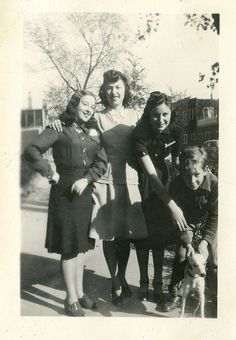 A group of youngsters posing with a cute little dog on the sidewalk, 1940s. Great 1940s dresses.