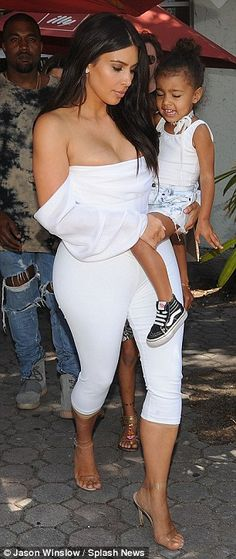 She's getting big: Kim confidently carried her growing toddler despite wearing very high heels but her flesh-colored Spanx were visible as her cropped tight leggings rode up her calves