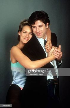 Jamie Lee Curtis holds onto John Travolta in publicity portrait for the film 'Perfect' 1985