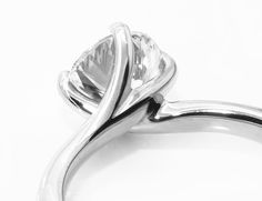 Close-up view of a four claw twist as seen from the side. Beautiful sweeping claw setting of this stunningly simple engagement ring design.