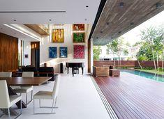 """""""A tradição arquitetônica modernista norteia o projeto da casa desenhada pelo escritório ONG & ONG, em Cingapura. Tanto é assim que o salão que une jantar e estar é  completamente aberto para o deque da piscina ao lado, e a laje não esconde o concreto que a constitui."""" (Casa Vogue Brasil)"""