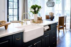 A blue kitchen island adorned with brass pulls topped with white marble fitted with a farm sink and polished brass faucet next to a built-in paper towel holder alongside a small jute rug.