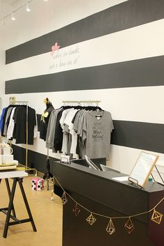 black and white horizontal stripe wall, black counter and gold clothes rack (Ikea painted gold)