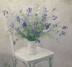 White chair, white pitcher, purple flowers