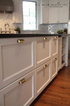 Brass bin pulls!  She placed the pulls at the top of each cabinet to make the cabinets look more like bins.  How smart!