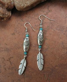 High quality silver-plated feathers dangle from long ornate boho/southwestern style silver beads accented by turquoise wood beads at each end.