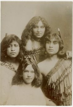 Photograph (black and white); portrait of four Maori girls wearing various styles of flax cloaks (a ngore cloak and pihepihe [?]), two have huia feathers in their hair; New Zealand. Gelatin silver print