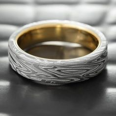 The ORGANIC WOOD pattern of this Damascus steel wedding ring is detailed and consistent all the way around. Unlike many Damascus rings on the market that only show full pattern on two sides of the ring, this gives you 360 degrees of detail. Classy, and original, the ORGANIC WOOD has a comfort fit 14K yellow gold liner that adds a rich, warm accent to this understated 7mm wide wedding band.