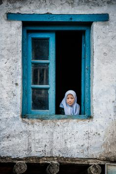 Pretty Muslim girl in blue window, Kargil, India
