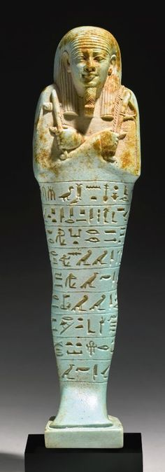 Egyptian pale blue faience ushabti of Neferibresaneith, 26th Dynasty, reign of Amasis, 570-526 B.C. Wab priest of the king, Royal Chancellor of Lower Egypt, Administrator of the Palace, and son of Shepen-Bastet, holding the hoe, pick, and seed-sack over his left shoulder, and wearing a braided beard with curled tip and striated tripartite wig, the nine lines of inscription beginning and ending at the back pillar, 18.4 cm high. Private collection