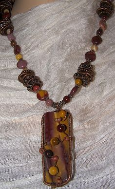 Love how the small beads create beautiful texture over the large pendant.