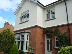 Transform the exterior of your property with our beautifully finished wooden windows. At Trustwood Joinery Manufacturers Ltd, we can manufacture and install windows in a range of styles, sizes and colours. 1930s House Exterior Uk, Dream House Exterior, Green Windows, House Windows, Bay Windows, Front Windows, Wooden Cladding Exterior, Bay Window Exterior, Rendered Houses