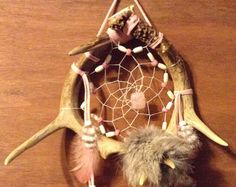 This dream catcher is made with 2 deer antlers has artificial sinew webbing with turquoise stone in the center of the web has turkey and rooster feathers attached with glass beads on the strands of buckskin and rabbit fur attached at the bottom measures 10 in. wide X 20 in. long has a total of 6 points
