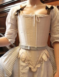 1770′s corset with lacing at the centre back, panniers with slits in the sides to reach the pocket and petticoat with placket fastening at the centre back.