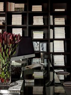 Glass desk,  Stacked collection of books & magazines,  very chic. Diego Revollo