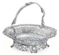 A GEORGE II SILVER CAKE BASKET  MARK OF SAMUEL HERBERT & CO., LONDON, 1752  Oval, on openwork base with masks and lion's-mask feet, the rim applied with grapevines and scrolls, the field engraved with a vacant neo-classical cartouche, the swing handle with dolphin joins, marked on reverse, also with scratch weight 56:10  14½ in. (36.7 cm.) long; 54 oz. 10 dwt. (1,706 gr.)