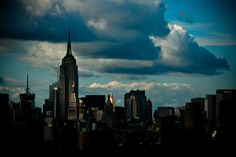 the empire state building and other buildings in downtown manhattan with strong afternoon storm lighting